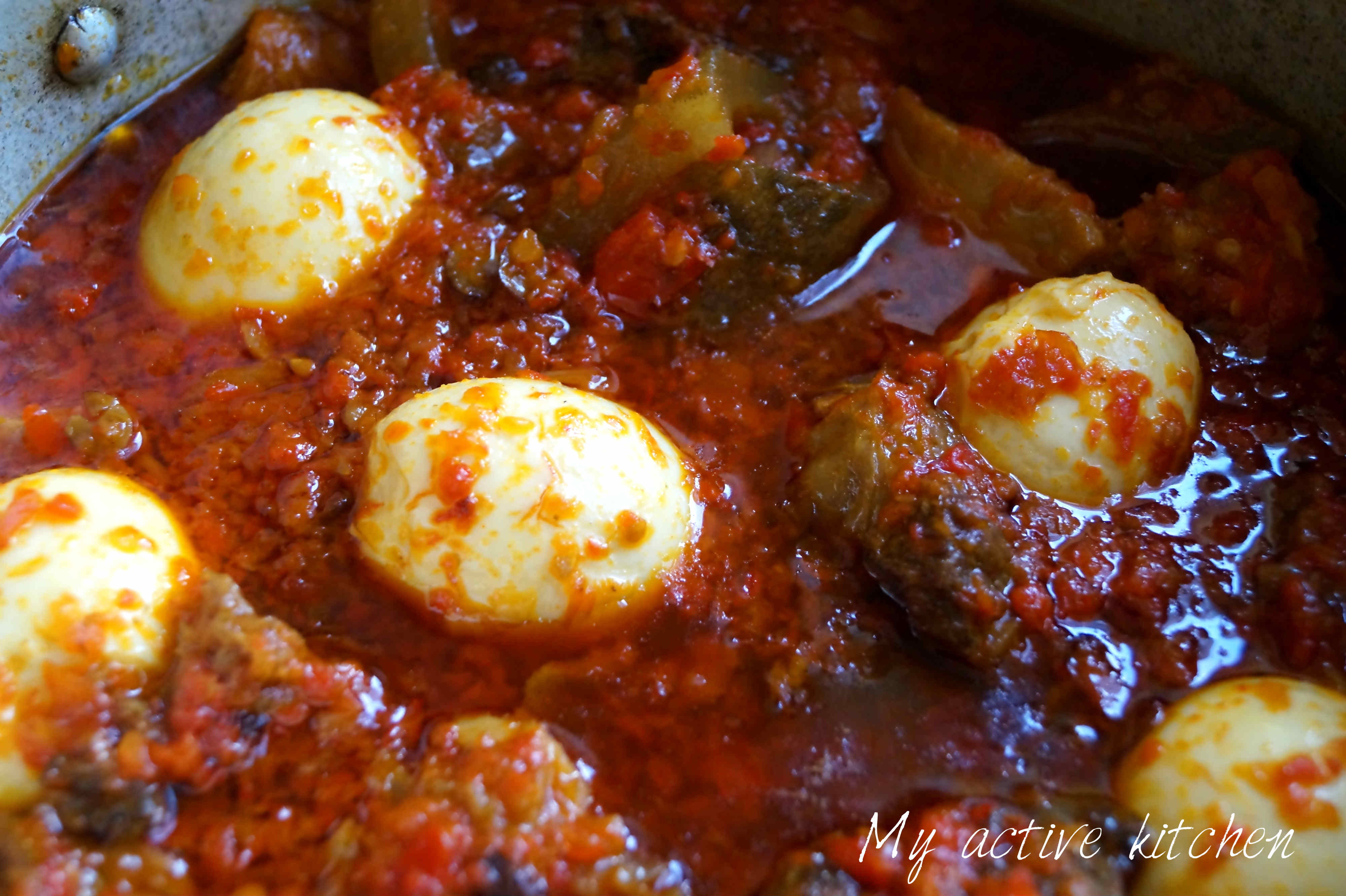 ofada stew with boiled eggs and assorted meat in pot