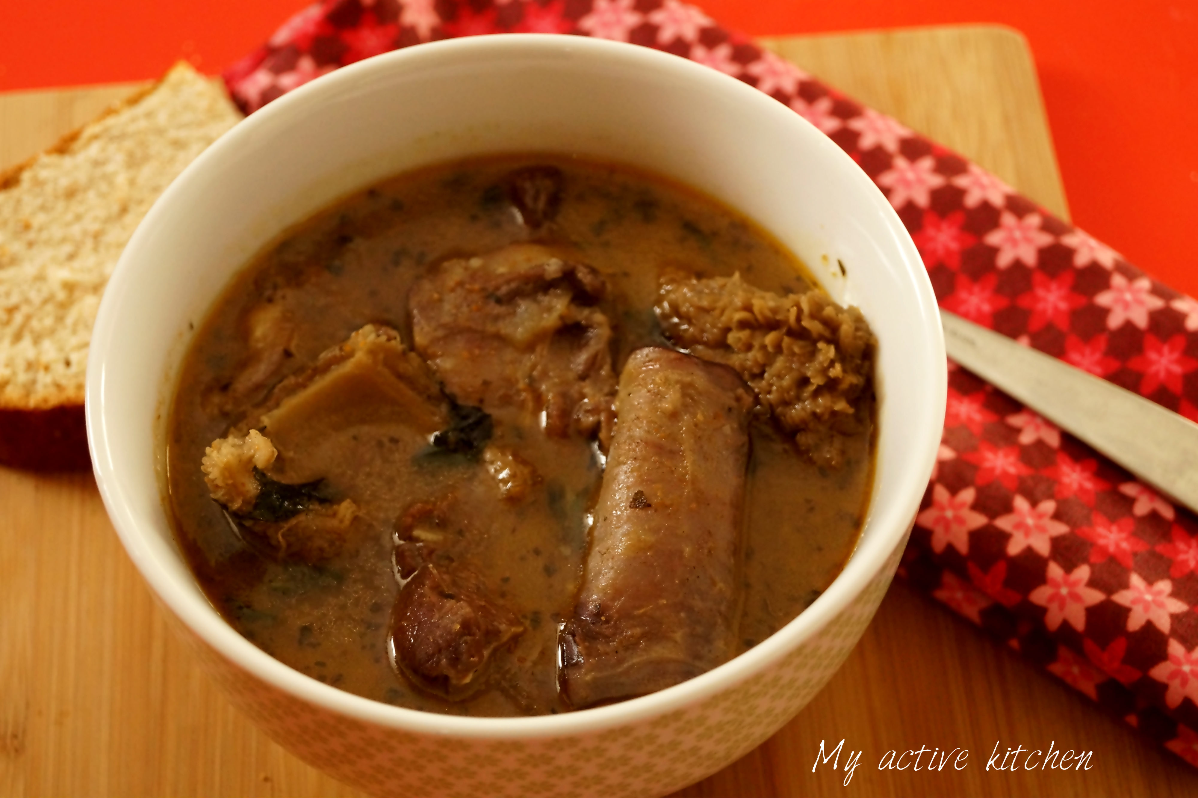 Nigerian assorted meat pepper soup in a white bowl placed on a red table. The bowl is placed beside a floral napkin and crusty bread