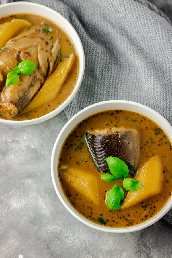 catfish pepper soup in two separate bowl placed on a coloured board with grey napkin thrown on the side of the bowls