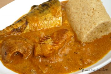 An angled photograph of ogbono soup loaded with mackerel, stock fish and ponmo