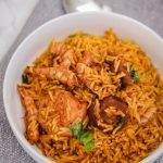 palm oil rice (local jollof rice) in a white bowl.