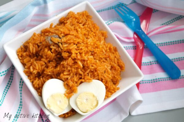 overhead shot of nigerian jollof rice and boiled egg cut in half