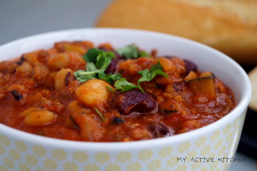 a close shot of bean chilli with a crusty french bread at the background