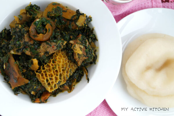 overhead shot of Edikang ikong in a white plate with a side of fufu