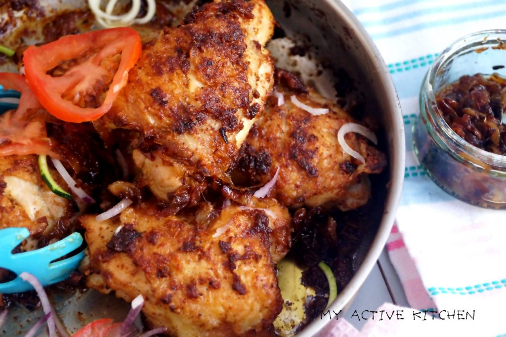 baked chicken suya in a skillet with a side of caramelised onions.
