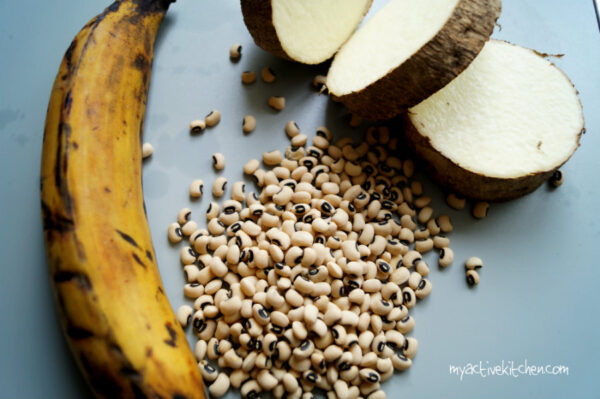 image of 1 ripe plantain, 3 slices of yam ans some black eyed beans on grey board