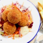 nigerian yam balls served over salad on a plate.