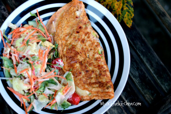spicy omelette on a white and black plate served with salad