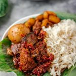 ofada stew with ponmo, assorted meat and egg soaked in stew. It is served with plain boiled rice.