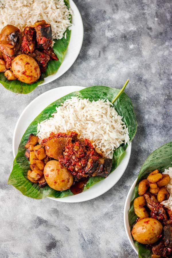ofada stew and rice served on a banana leaf.