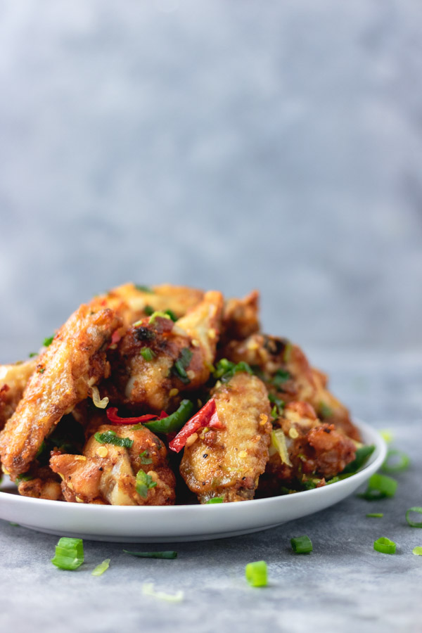 salt and pepper chicken wings on a plate placed on a blue surface.
