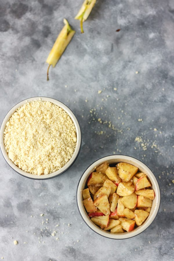 apple crumble in two ramekins. one of the apple crumble image have the toppings while the other have the just apples