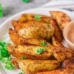 Well seasoned crispy potato wedges!! These crispy potatoes are sinfully good. Not only are they crispy on the outside, they are well seasoned and fluffy on the inside. The best part is they are baked and not fried!!! #easypotatorecipe #potatowedges #healthypotatowedges #healthyfrenchfries