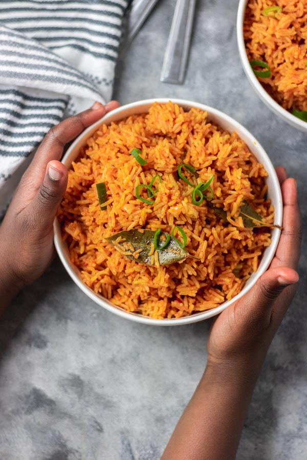Hands over a bowl of coconut jollof rice