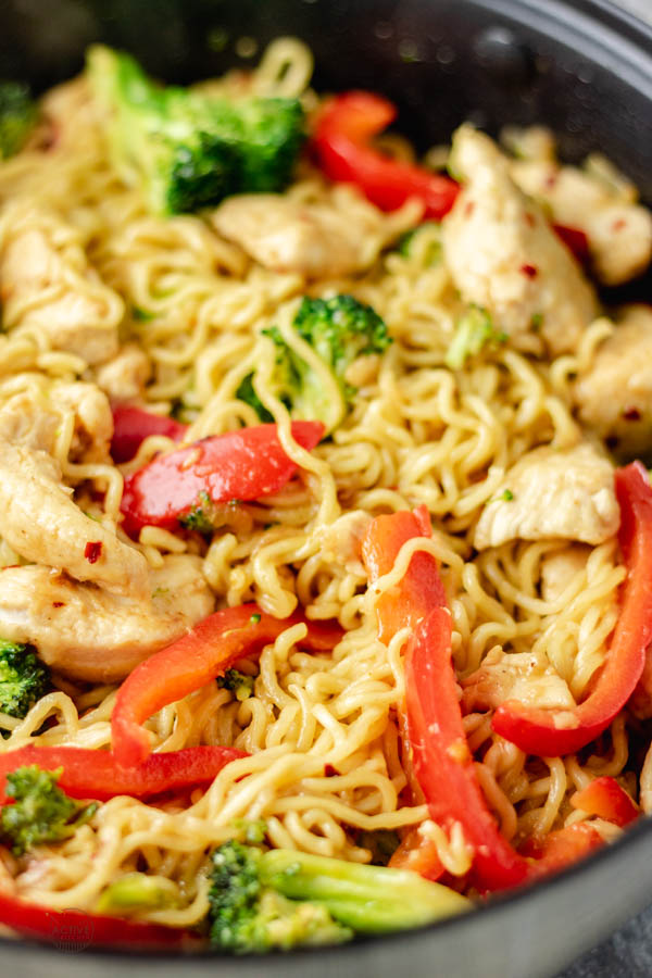 overhead shot of chicken ramen noodle stir fry in a skillet made with broccoli and bell pepper and stir fry sauce.