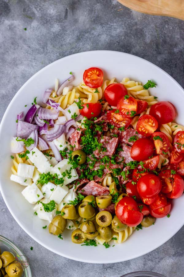 overhead shot of an Italian pasta salad in a white bowl.