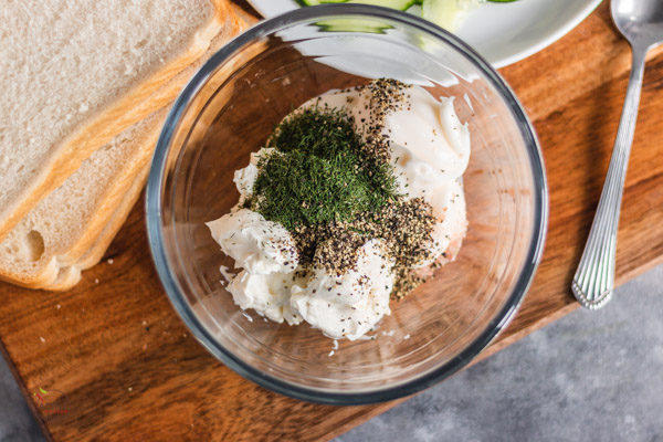 cream cheese, dill, black pepper and mayonnaise in a bowl placed on a board alongside slices of bed.