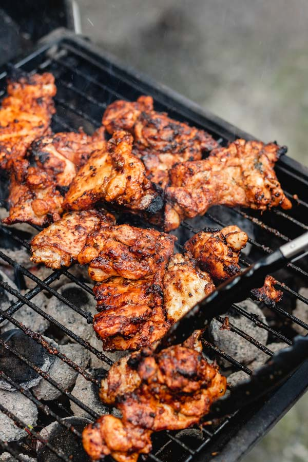 Grilled boneless chicken thigh on a coal barbecue.