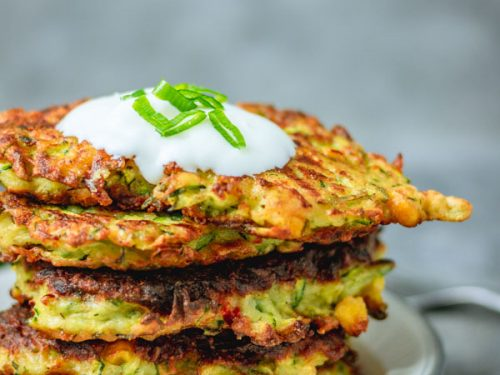 stack of crispy courgette and sweetcorn fritters on a plate.