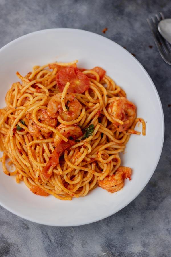 a plate of spaghetti jollof and shrimps.