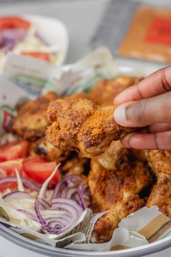 a hand holding chicken drumette.
