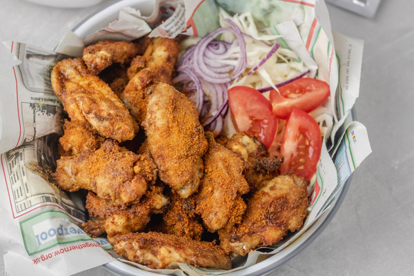 chicken wings suya served on old newspaper in a bowl with some salad on the side.