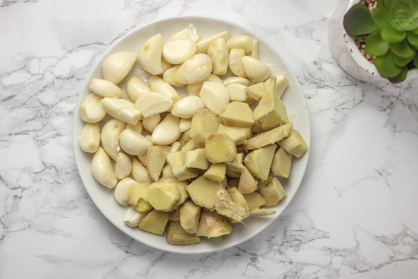 peeled garlic and ginger on a white plate.