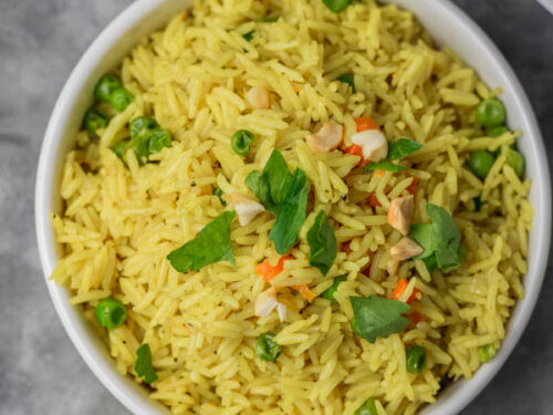 a bowl of yellow rice garnished with parsley and cashew nuts.