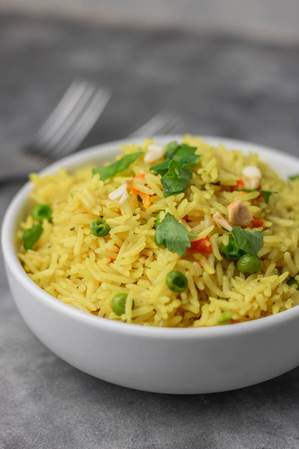 a bowl of yellow rice garnished with parsley and nuts.