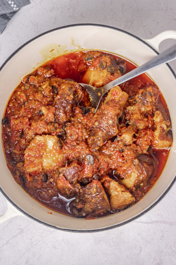 a ladle in a pot of fried stew.